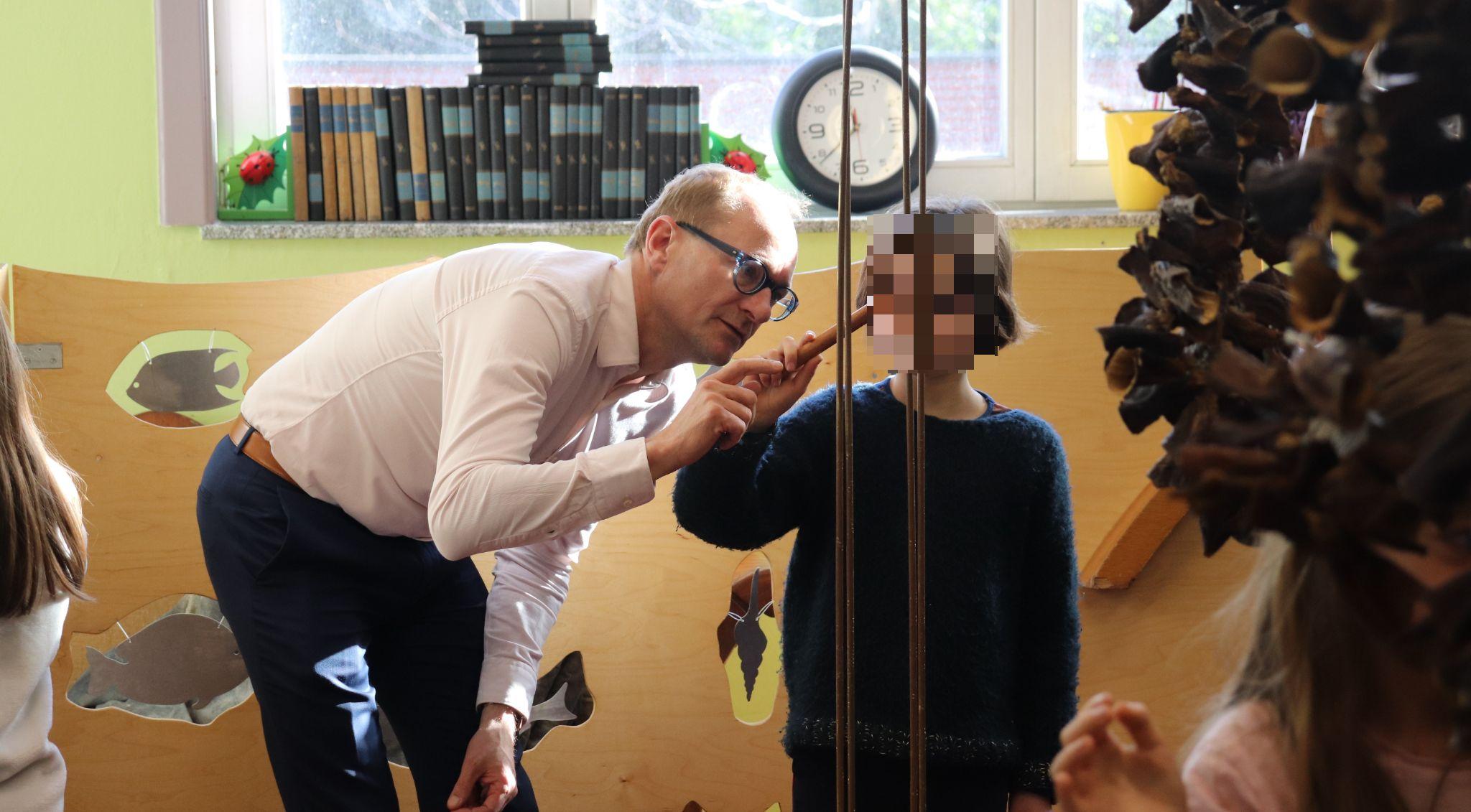 De minister bespeelt een instrument met een leerling