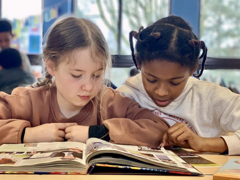Leerlingen lezen een boek in de klas