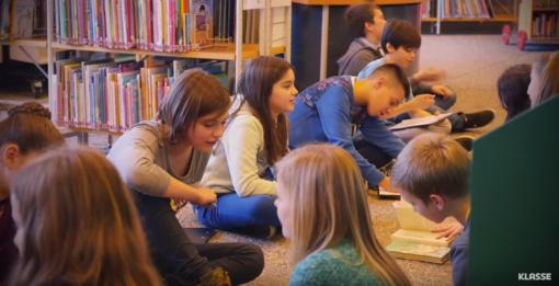 Leerlingen lezen boeken op de vloer van de bibliotheek