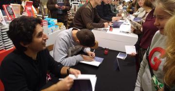 Mustafa Kör en leerlingen signeren hun boek Poëziejongens op de Boekenbeurs