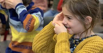 Een rij kinderen zijn aan het zingen. Ze houden hun handen als een soort van schelp voor hun mond. Zo kunnen ze beter horen hoe ze zelf zingen.