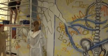 Leerlingen maken een graffiti-kunstwerk in de gang van hun school