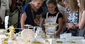 Ouders en leerlingen kijken op de tentoonstelling naar de maquette die de leerlingen maakten