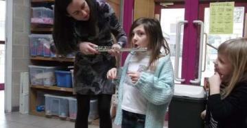 Juf houdt dwarsfluit vast terwijl kind erin blaast