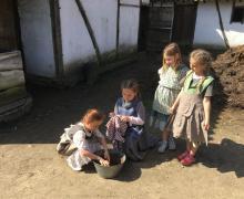 4 meisjes, gekleed in kledij van 100 jaar geleden, wassen kleren in een metalen kuip
