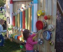 Kinderen maken muziek op trommels en buizen in de buitenspeelplaats