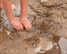 Kind speelt in nat zand