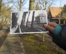 Leerling houdt een oude foto van Grimbergen voor dezelfde plaats vandaag