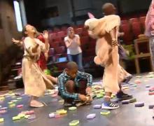 Kinderen lopen rond op het podium. Op de vloer liggen sponsjes.
