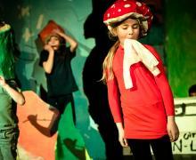 Meisje op podium met een zelfgemaakte paddenstoel als hoed