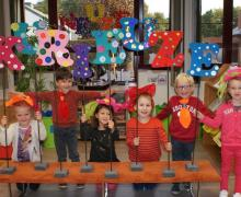 Zes kleuters poseren met de letters van 'Kurieuze Neuzen' die ze knutselden en versierden met kleurrijke bloemetjes, bolletjes en googly eyes.