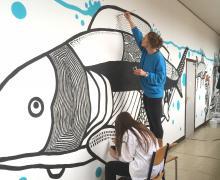 Op een muur schilderen twee leerlingen een walvis