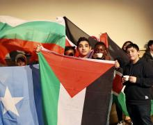Leerlingen van de OKAN-klas houden elk een vlag van hun land van herkomst omhoog