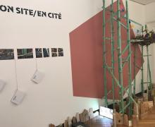 De kleine houten huisjes, de toren en het nest van de studenten staan naast elkaar tegen een muur. Op de muur staat 'On site / en cité'.