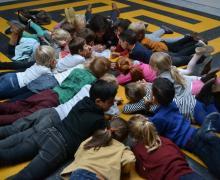 Kinderen in een kring luisteren naar voorlezer