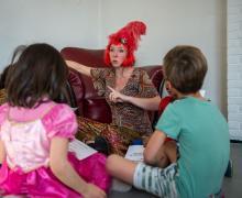 Leerkracht met rode pruik geeft les. de leerlingen zitten in een cirkel rond haar.