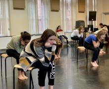 Leerlingen zitten op een stoel in de balletzaal. Eén leerling zit met het ellebogen op de knieën en steunt met de kin op de handen.