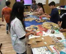 Je ziet leerlingen rond een tafel staan. Ze knippen maskers uit karton. Er ligt veel rommel op de tafel.