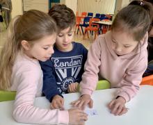 Drie leerlingen staan aan een tafel. ze proberen een woord te vormen met letters die voor hen liggen.
