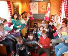Boekenjuf Frie tussen lezende leerlingen in de leescaravan
