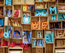 Een wand met kartonnen dozen. In elke doos zie je een gekleurde letter staan.
