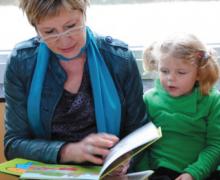 Boekenjuf Agnes leest een boek voor aan een kleuter