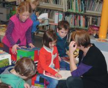 Een juf leest een boek voor in de klas