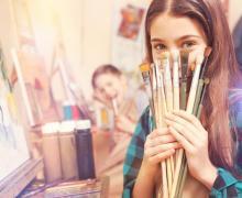 Je ziet een meisje met lange haren. In haar handen houdt zij een aantal penselen vast die zij voor haar mond houdt.