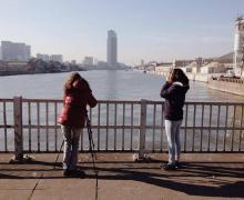 2 leerlingen nemen vanop brug foto van het water en de skyline