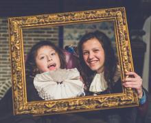 2 kinderen met een molensteenkraag rond hun nek poseren voor een foto achter een gouden kader