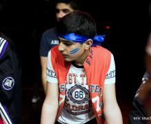 OKAN-leerling draagt blauwe bandana en heeft 2 blauwe strepen op zijn wangen