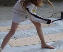Meisje gooit verf op houten plaat