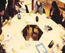 Leerlingen zitten rond tafel voor brainstorm
