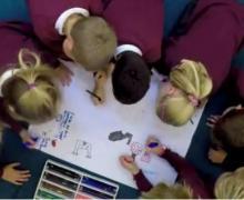 Groep leerlingen in uniform, tekent samen op een groot blad papier.