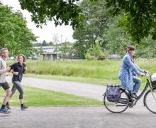 Joggers lopen achter een fietser aan