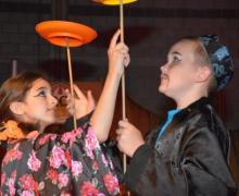 Verklede kinderen jongleren borden op een stok
