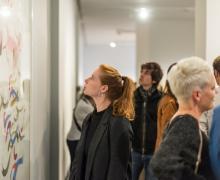Vrouw kijkt naar kunstwerk tijdens een tentoonstelling
