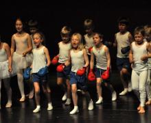 Kinderen verkleed als balletdansers en boksers op podium
