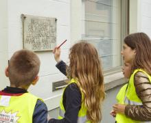 Leerlingen lezen tekst op huisgevel: 'Hier leefde en werkte de letterkundige Marcel Matthijs 1899-1964'.