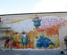 Graffitimuur met vogels op. Op de muur staat ook volgende tekst gespoten: 'Kleine Icarus doet zijn ogen open en wat ziet hij? Allemaal kinderen die spelen, lachen, dansen, zingen, springen, laa laa prachtig gewoon.'