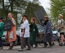 Kinderen in kleren van de jaren '70 wandelen in stoet. Het meisje van voren in de stoet heeft een bord met 'Café de pluim 1978' vast