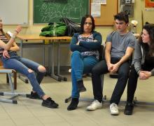 Leerlingen zitten neer op een stoel middenin een scène
