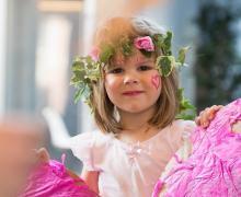 Meisje met bloemenkrans op het hoofd en een roos hartje geschilderd op de wang