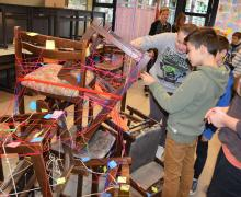 Leerlingen kijken naar hoop stoelen vastgebonden met touwtjes