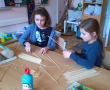 2 leerlingen verbinden houten stokjes met elastiekjes