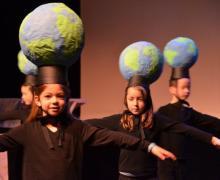 Kinderen op podium dragen hoed met geknutselde wereldbol op