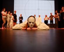 Leerling met wit masker op ligt neer op podium