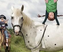 Meisje verkleed als Pipi Langkous doet handstad op een paard