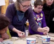 Leerlingen en juf knutselen met klei