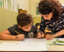 Jongen kijkt aandachtig hoe Laïla zijn naam in het Arabisch schrijft